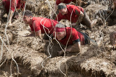 Team of Racers Crawling Through Electric Obsticle Stock Images