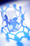 Team Rallies Around Idea. Group of blue paper cut-out stick figures form a ring around a white light bulb Royalty Free Stock Image
