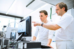 Team of researchers carrying out experiments in a lab Stock Photos