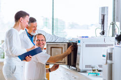 Team of researchers carrying out experiments in a lab Royalty Free Stock Photo