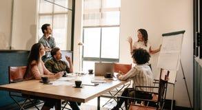 Team a reunião na sala de reuniões para explorar estratégias empresariais novas foto de stock