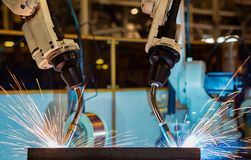 Team robots are welding  part in car factory. Industrial robots are welding car part in automotive industrial factory Stock Images