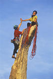 Team of rock climbers reaching the summit. Stock Photo