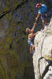Team of rock climbers reaching the summit. Royalty Free Stock Images