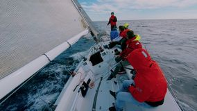 Team of sailors skippers on deck of sailboat yacht
