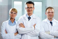 Team of scientists. Three positive scientists looking at camera and smiling Stock Photos