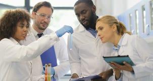 Team Of Scientists Analyzing Different-Vloeistoffen in Reageerbuizen die Nota's die over Onderzoek maken in Modern samenwerken stock video