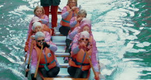 Team of senior women rowing. VENICE, ITALY - FEBRUARY 18, 2015: Team of senior women in life-jackets rowing in the water of canal with male trainer watching them stock video footage