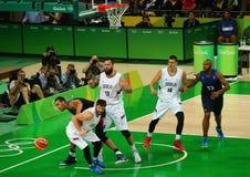 Team Serbia no branco e equipe França na ação durante o fósforo de basquetebol do grupo A do Rio 2016 Jogos Olímpicos Foto de Stock Royalty Free