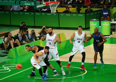 Team Serbia in white and team France in action during group A basketball match of the Rio 2016 Olympic Games Royalty Free Stock Photo