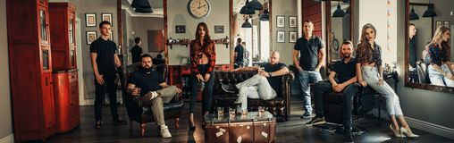 Team from seven barbers in modern barbershop. royalty free stock image