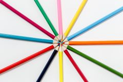 Team of colored pencils lined with rays on white background stock photography