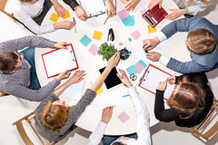 Team sitting behind desk, checking reports, talking. Top View. The business concept of collaboration, team work, meeting Stock Photos
