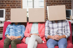 Team sitting on couch with boxes over heads Stock Photos