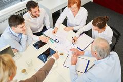 Team sitting together in business meeting stock photography