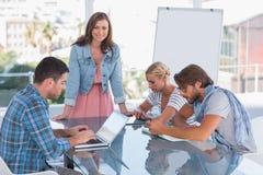 Team, Sitzung mit einer Frau habend, die an der Kamera lächelt Stockfotos