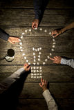Team of six business men and women joining forces and effort to. Assemble a light bulb shape with blank puzzle pieces by a lit desk lamp on a textured wooden stock photography