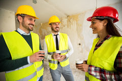 Team of smiling architects at coffee break. Construction site Royalty Free Stock Image