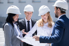 Team of smiling architects in hard hats working together with blueprint. Professional team of smiling architects in hard hats working together with blueprint Royalty Free Stock Photos