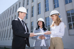 Team of smiling architects holding blueprint while standing together. Professional team of smiling architects holding blueprint while standing together Royalty Free Stock Photography