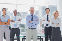 Team of smiling business people standing with arms folded stock photo