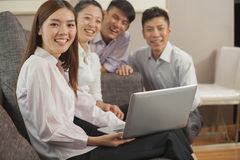 Team of smiling business people working together on laptop Stock Image