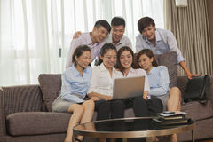 Team of smiling business people working together and looking at one laptop Stock Image