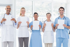Team of smiling doctors looking at camera and holding paper Royalty Free Stock Images