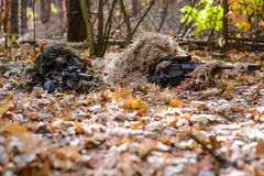 Team of snipers aiming at target in forest. Two sniper in camouflage suits with rifles in hands hide in the woods stock photography