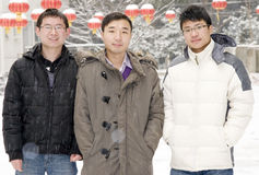 Team  in snow. Three young man with coats in snow day in winter,background is some red lanterns Stock Photos