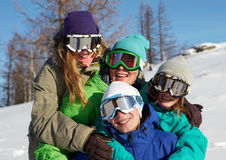 Team of snowboarders. Portrait of four young people in ski goggles embracing Stock Image