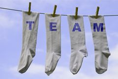 Team socks. Four white socks pegged on a clothes line with the words Team on them Stock Image