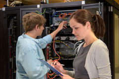 Team of IT specialists in datacenter. Working by network servers Royalty Free Stock Photo