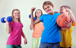 Team of sportive kids friends with dumbbells and ball. Team portrait of sportive kids friends with dumbbells and ball Royalty Free Stock Image