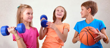 Team of sportive kids friends with dumbbells and ball Stock Photography