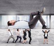 Team stützt Chef im Büro Stockfoto