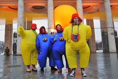 A team of street actors in carnival costumes pose for photos royalty free stock photo