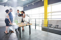 Team of successful business people having a meeting in executive sunlit office Royalty Free Stock Photos