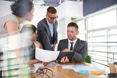Team of successful business people having a meeting in executive sunlit office Royalty Free Stock Photography