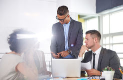 Team of successful business people having a meeting in executive sunlit office Stock Image
