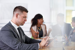 Team of successful business people having a meeting in executive sunlit office Stock Images