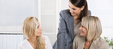 Team: Successful business team of woman in the office talking to Stock Images