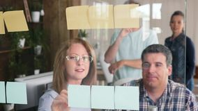 Team of successful people sharing great ideas on their sticky notes on a glass door