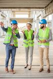 Team of successful architects and business partners taking a tour of the construction site stock photo