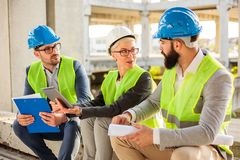 Team of successful young architects discussing project details during a meeting stock image