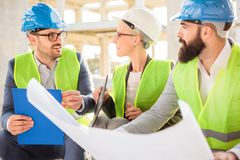 Small team of architects visiting a construction site, looking at blueprints stock photography