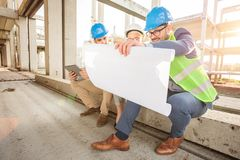 Group of young architects looking at floor plans during inspection of a construction site stock photo
