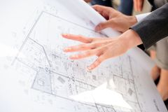 Young female architect showing floor plans to colleagues on a construction site. Close up. stock photography