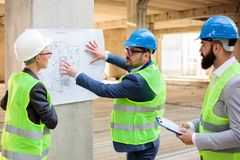 Team of architects and business partners looking at architectural drawings and blueprints. Team of successful young architects and business partners during a stock photos