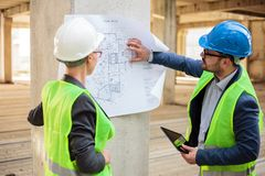 Two successful young architects looking at blueprints on a construction site royalty free stock images